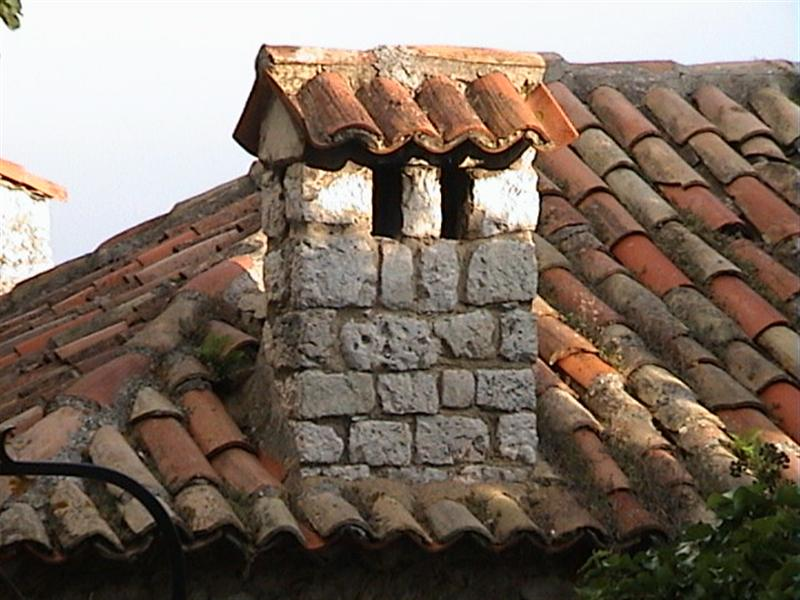 Close up of brick chimney on a tiled roof in San Paul de Vence