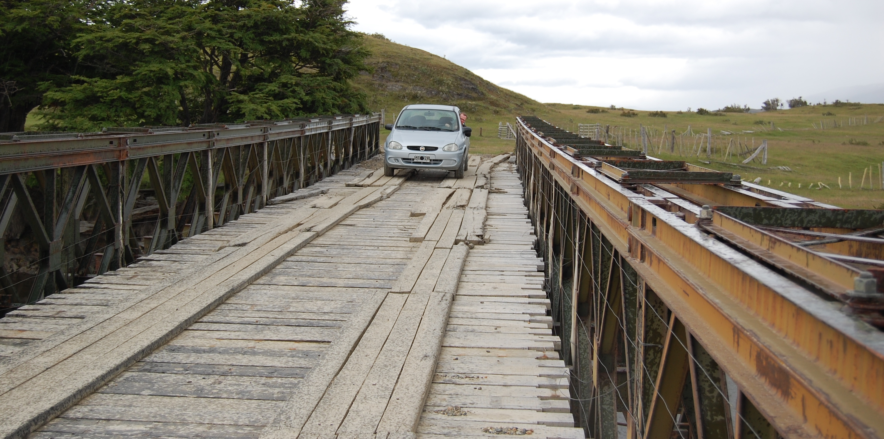A wooden bridge, with a small car passing precariously over it.