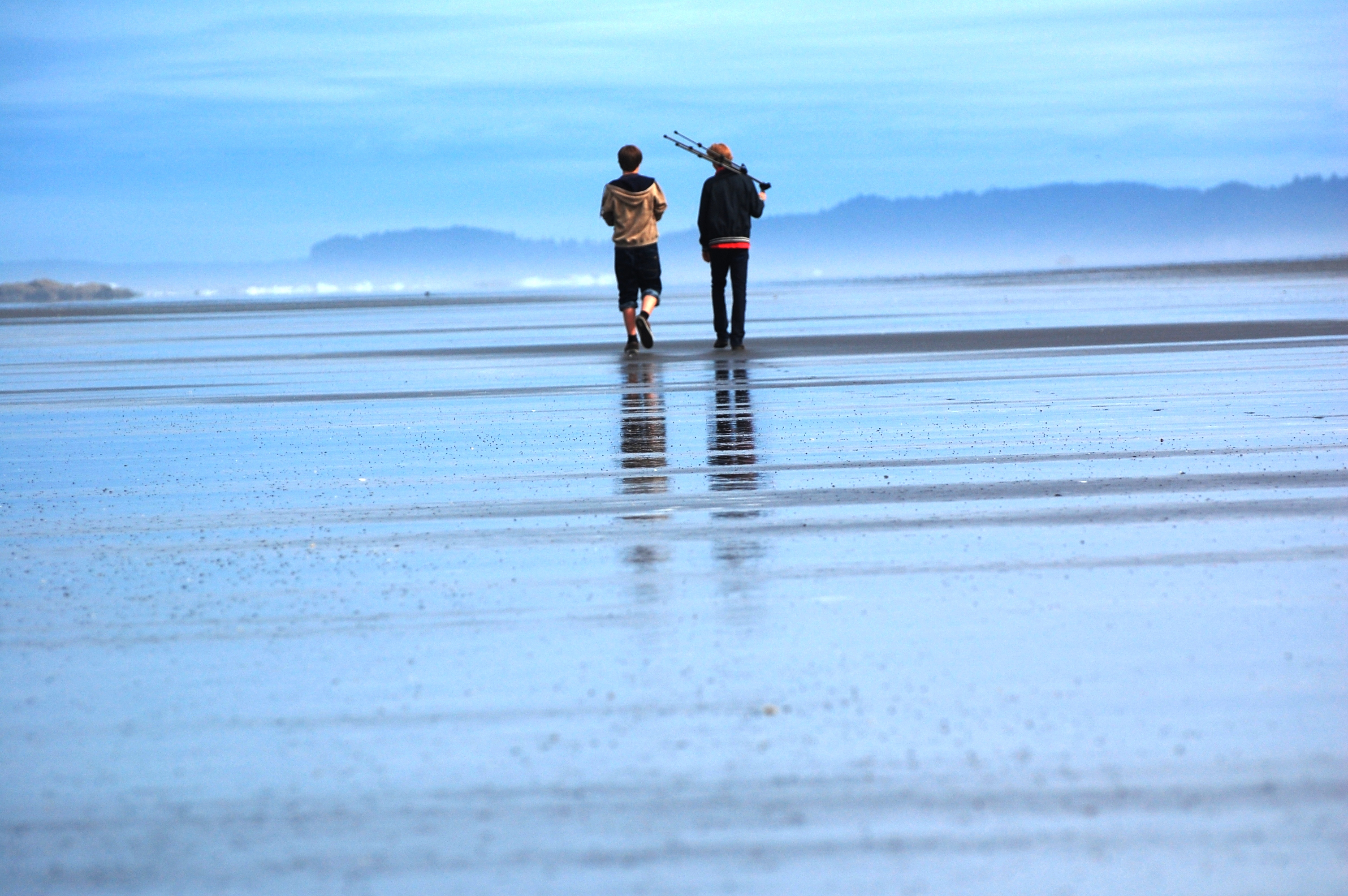 Two boys walking on a wet sand beach. Framed by the blue water and blue sky.