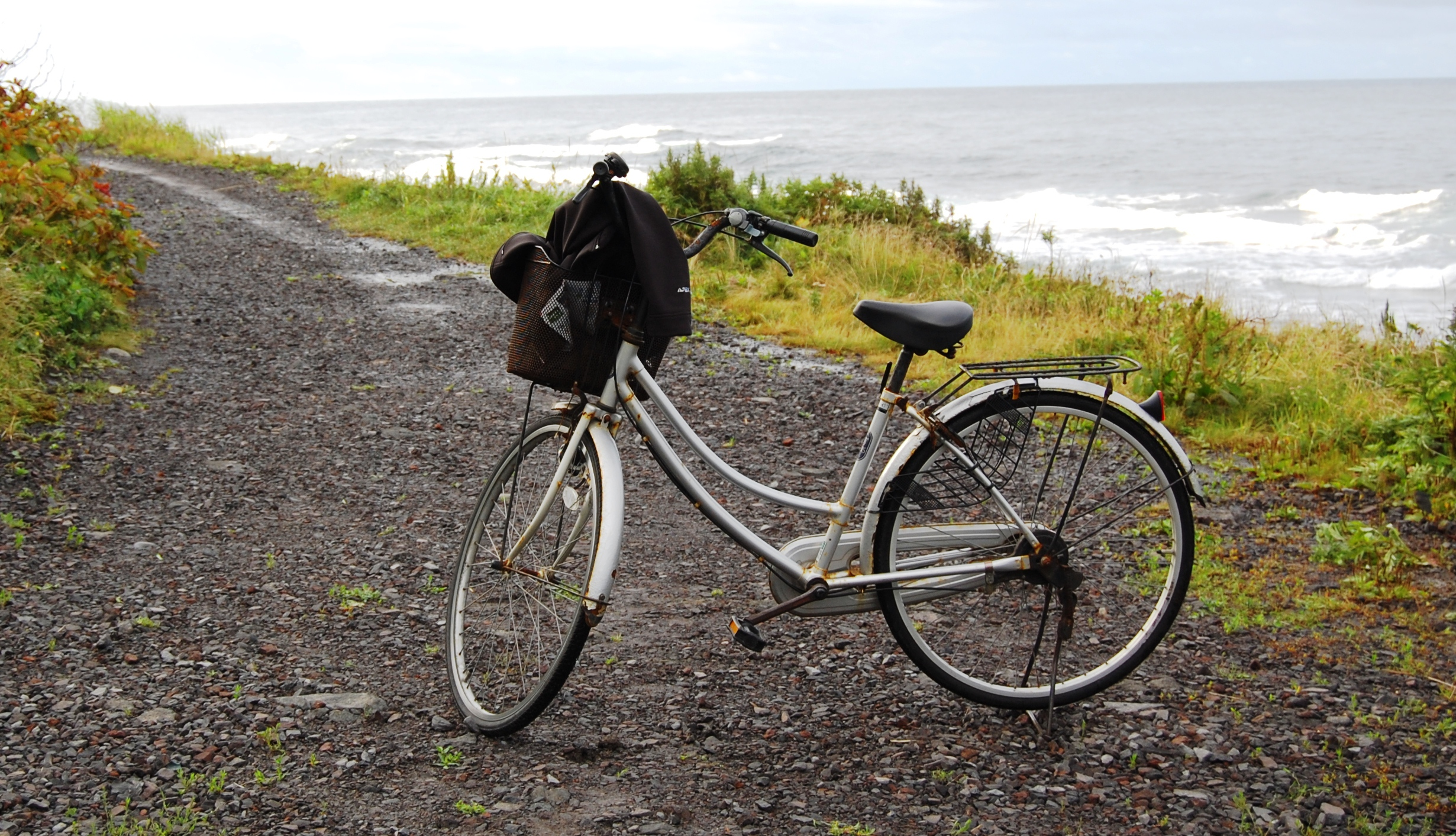 An old bicycle with a handlebar basket, on a gravel road next to the Pacific Ocean, Japan.