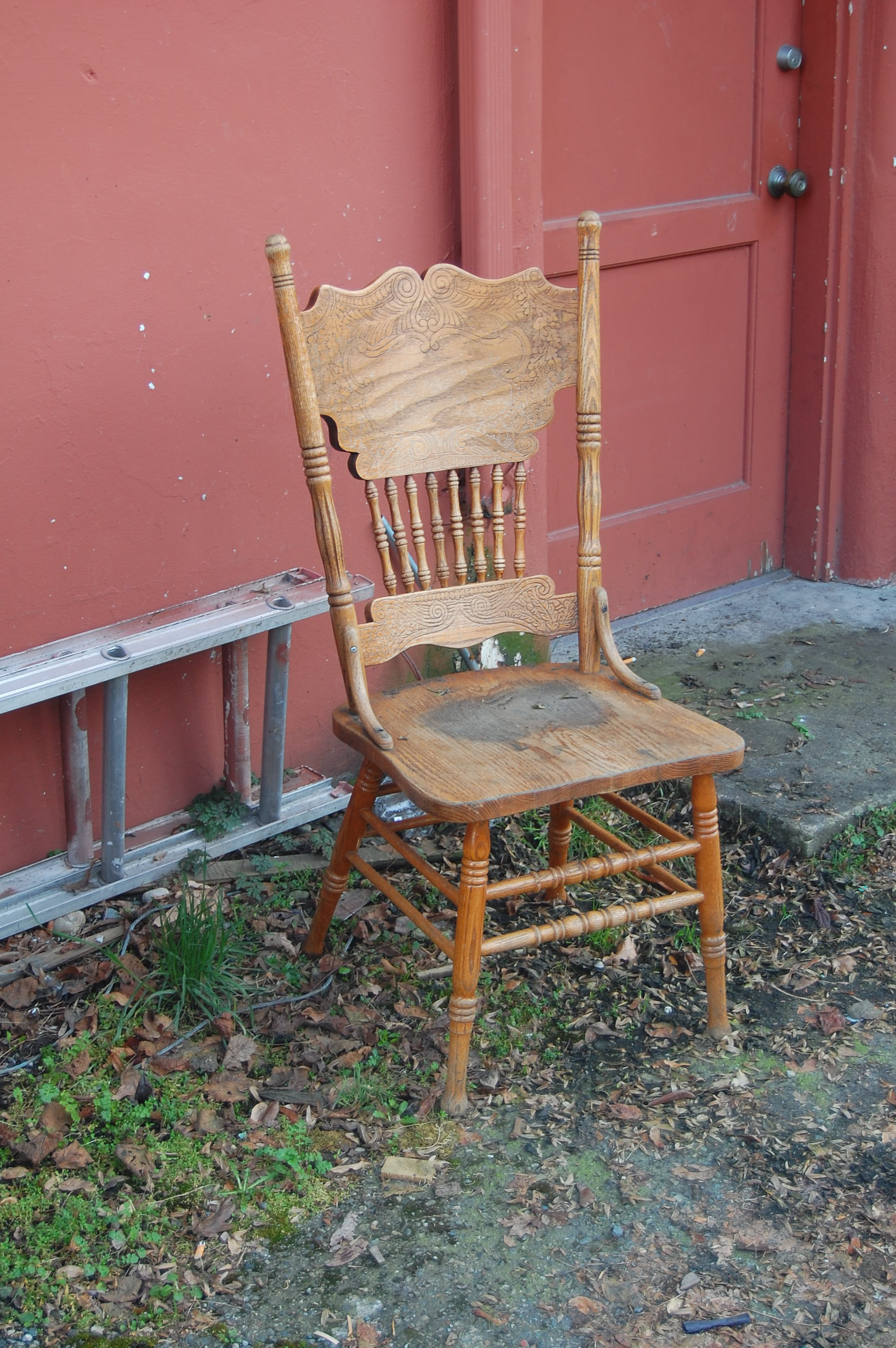An old wooden chair outside a red door